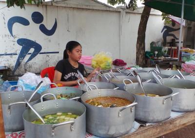 Deze mevrouw heeft pannen gekocht om eten te kunnen koken. Ze verkoopt het in de stad