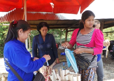 Met een microkrediet kocht deze mevrouw bamboesstokken. Ze vult ze met rijst en groente en verkoopt ze met winst